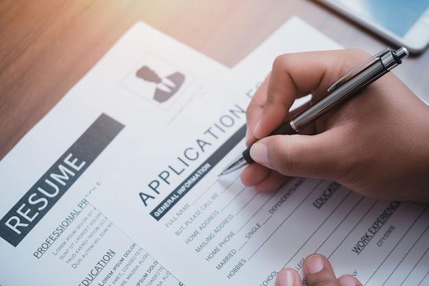 Conceito de formulário de inscrição de emprego na web on-line. close de um empresário irreconhecível, sentado à mesa, fazendo anotações no formulário de inscrição