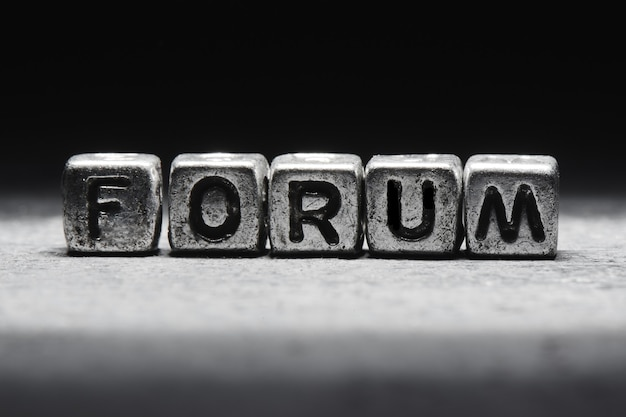 Conceito de fórum. a inscrição em cubos 3d de metal isolados em um fundo preto, estilo grunge