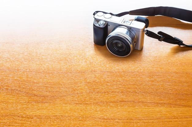 Conceito de fotografia digital com câmera mirrorless na mesa de madeira com espaço para texto