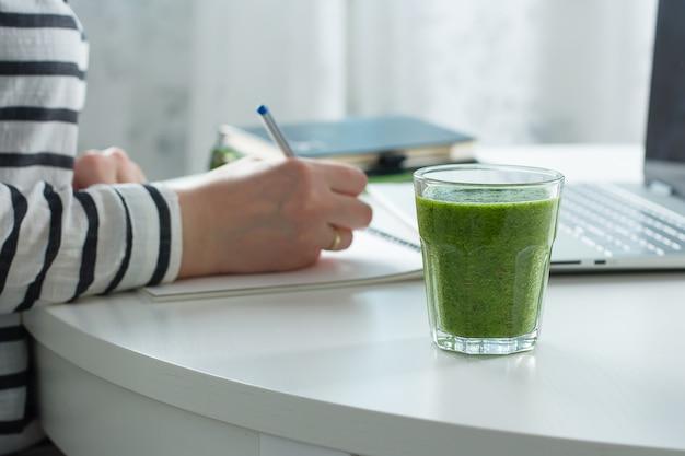 Conceito de freelancer de lição de casa. mulher escrevendo no notebook, laptop nas proximidades. smoothie verde saudável