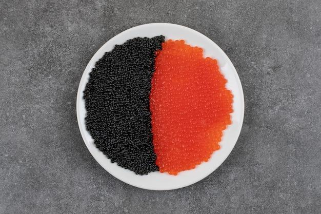 Conceito de frutos do mar. caviar vermelho e preto na chapa branca.