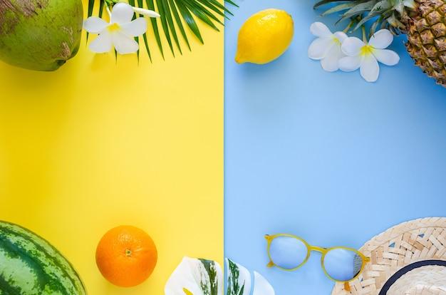 Conceito de fundo de verão com chapéu de praia, óculos de sol, flores de abacaxi, limão, coco, melancia, laranja e frangipani em fundo amarelo e azul