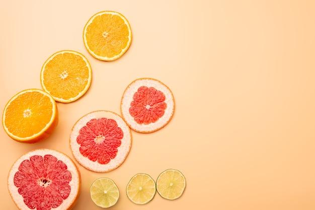 Conceito de fundo de verão em fatias de laranja, toranja, limão e lima em fundo laranja