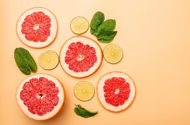 Conceito de fundo de verão fatiado toranja, limão e hortelã em fundo laranja