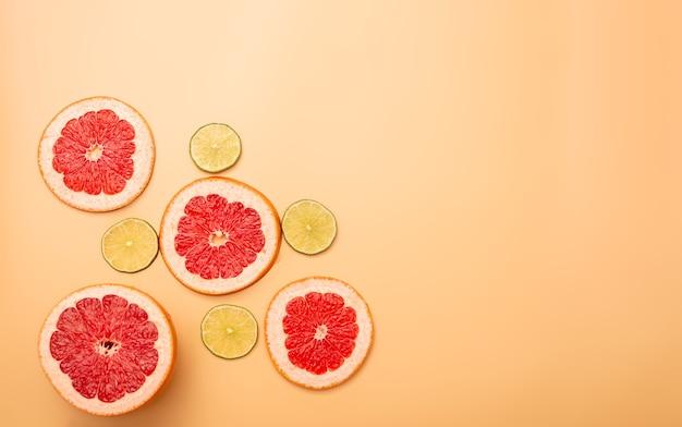 Conceito de fundo de verão fatiado toranja, limão em fundo laranja