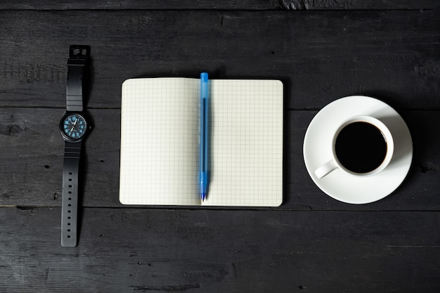 Conceito de gerenciamento de tempo. bloco de notas, xícara de café e relógio mecânico, vista superior