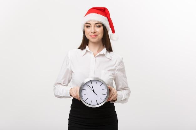 Conceito de gerenciamento de tempo - jovem mulher de negócios feliz com chapéu de papai noel segurando um relógio isolado sobre a parede branca.