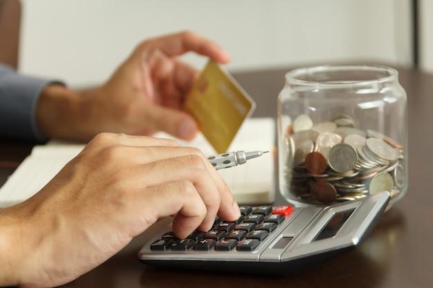 Conceito de gestão de dinheiro. mão homem usa calculadora para calcular os orçamentos para pagar o departamento de cartão de crédito.