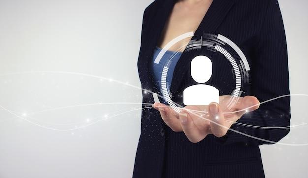 Conceito de gestão de rh de recursos humanos. mão segure o holograma digital humano em fundo cinza, organização empresarial e hierarquia de pessoal.