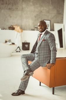 Conceito de gestão hoteleira, trabalhador americano africano, senta-se no saguão de trabalho corretamente organizado ...