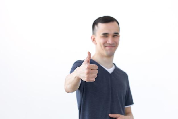 Conceito de gesto e pessoas - homem asiático com sorriso aparecendo o polegar na superfície branca com cópia