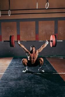 Conceito de ginásio com homem forte levantando a barra