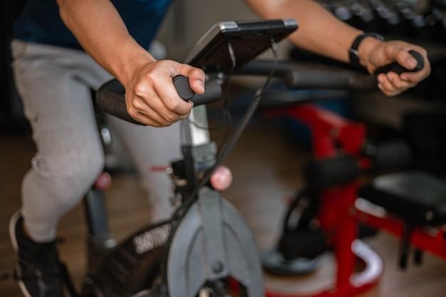 Conceito de ginásio de treinamento um adolescente do sexo masculino fazendo exercícios cardiovasculares na máquina de ciclismo no ginásio como sua rotina saudável. Foto Premium
