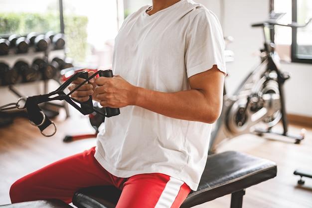 Conceito de ginásio de treinamento um adolescente do sexo masculino, usando um equipamento de ginástica, puxando seus braços musculosos contra a máquina.