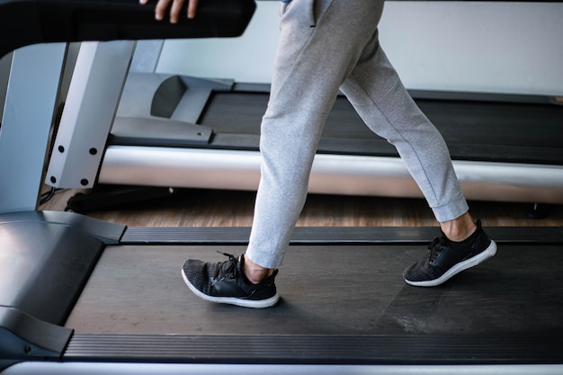Conceito de ginásio de treinamento um adolescente do sexo masculino, vestindo calças compridas e tênis pretos, andando em uma esteira para treino cardiovascular.