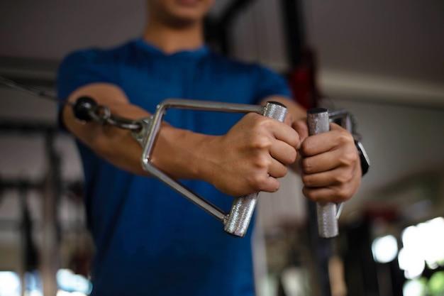 Conceito de ginásio de treinamento um adolescente masculino musculoso usando um equipamento de ginástica repetindo empurrando para frente para desenvolver seu peito.