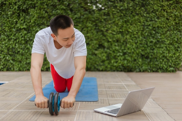 Conceito de ginásio de treinamento um jovem adulto do sexo masculino fazendo exercício enquanto estava nas redes sociais com seu laptop durante uma pandemia covid-19.