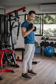 Conceito de ginásio de treinamento um jovem adulto usando seu braço forte e musculoso, levantando um haltere para cima e para baixo no ginásio.
