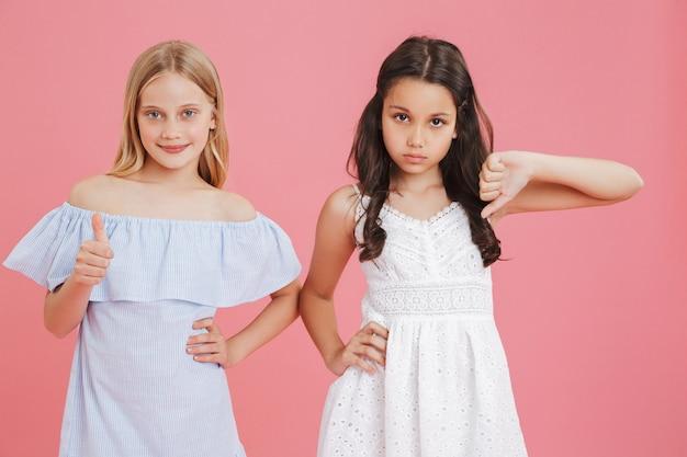 Conceito de gosto e não gosto. meninas morenas e loiras de 8 a 10 anos em vestidos que expressam diferentes emoções com o polegar para cima e para baixo.