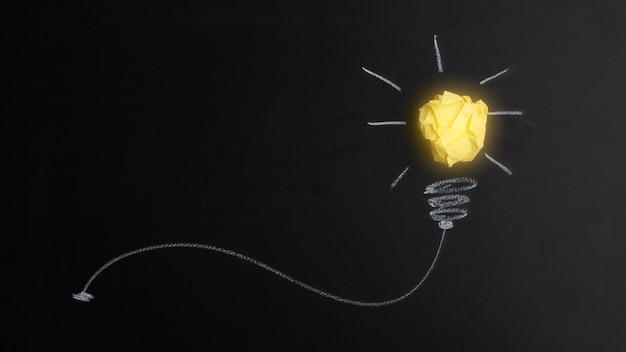 Conceito de grande ideia com lâmpada de papel amarelo amassado isolada em fundo escuro. idéia criativa. conceito de ideia, inovação e inspiração.