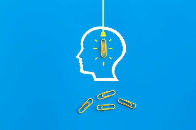 Conceito de grandes idéias com cérebro humano, clipe de papel, pensamento, criatividade, lâmpada sobre fundo azul, novo conceito de idéias
