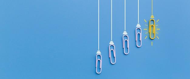 Conceito de grandes idéias com clipe de papel pensando criatividade lâmpada sobre fundo azul