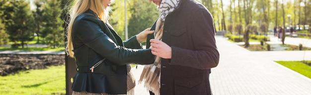 Conceito de gravidez elegante - close-up do retrato de casal de marido e mulher descolados em roupas da moda, caminhando no parque da cidade