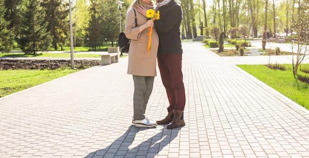 Conceito de gravidez elegante de close-up - retrato de casal de marido e mulher descolados em roupas da moda, caminhando no parque da cidade