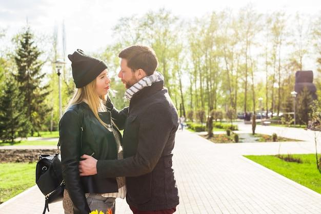 Conceito de gravidez elegante - retrato de casal de descolados marido e mulher em roupas da moda, andando no parque da cidade.