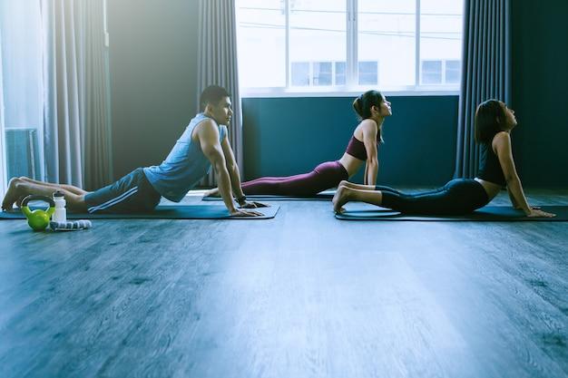 Conceito de grupo de ioga; jovens praticando ioga em sala de aula; sentir-se calmo e relaxar na aula de ioga