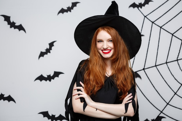 Conceito de halloween - bruxa bonita segurando a mão e sorrindo sobre a parede cinza.