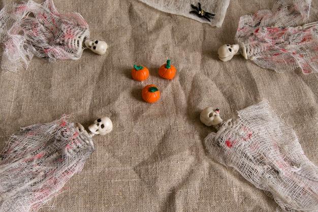 Conceito de halloween com abóbora, esqueleto e aranhas de brinquedo em fundo cinza amassado.