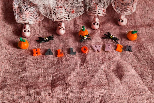 Conceito de halloween com abóbora, esqueleto e aranhas de brinquedo em um fundo cinza amassado