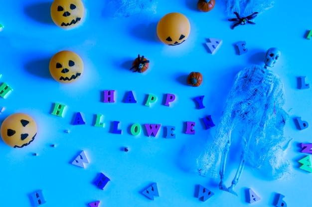 Conceito de halloween com abóboras, esqueleto, aranhas de brinquedo e letras de feliz dia das bruxas sobre fundo azul.