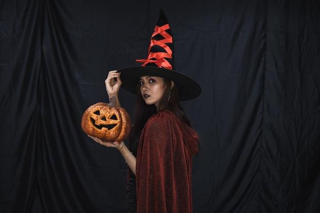 Conceito de halloween da jovem mulher asiática na fantasia de bruxa e segurar a abóbora de halloween laranja em fundo de pano preto. retrato de mulher adolescente vestida de bruxa para celebrar o festival de halloween.