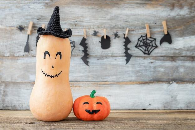Conceito de halloween de duas abóboras com caretas em um fundo de férias de madeira