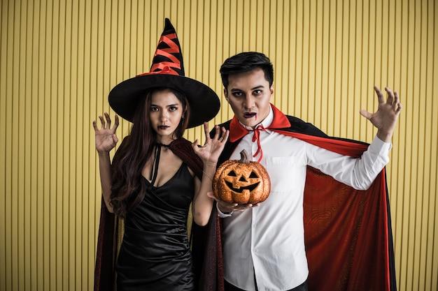 Conceito de halloween de uma jovem mulher asiática na fantasia de bruxa e o homem asiático na fantasia de drácula em fundo amarelo. casal adolescente do retrato vestido de bruxas e drácula para celebrar o festival de halloween.