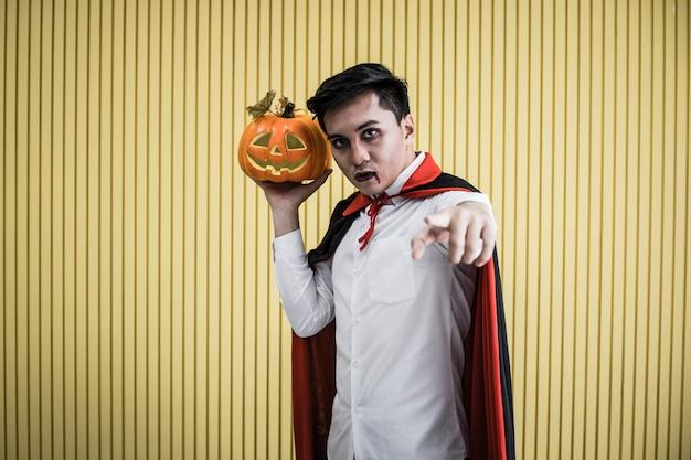 Conceito de halloween do jovem asiático em traje de drácula e segurar a abóbora de halloween laranja em fundo amarelo. retrato de homem adolescente vestido de drácula para comemorar o festival de halloween.