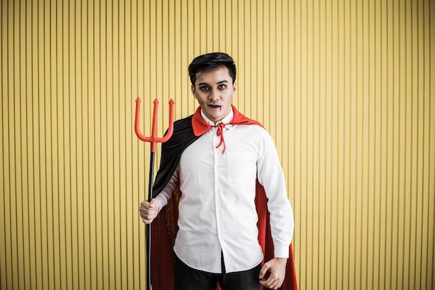 Conceito de halloween do jovem asiático em traje de drácula e segurar a lança sobre fundo amarelo. retrato de homem adolescente vestido de drácula para comemorar o festival de halloween.