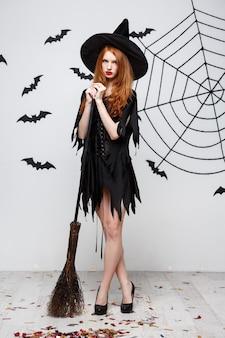 Conceito de halloween feliz e elegante bruxa gosta de brincar com vassoura festa de halloween sobre parede cinza