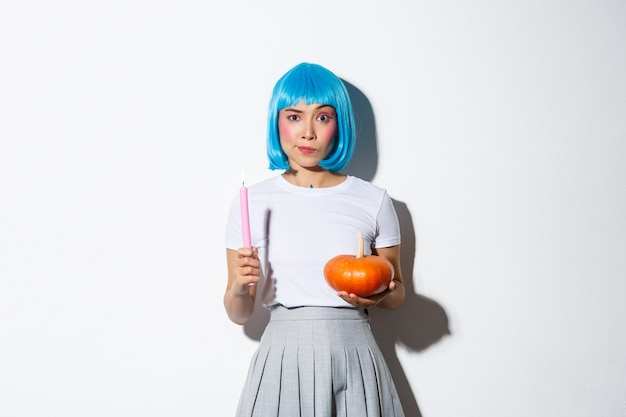 Conceito de halloween. imagem de uma atraente garota asiática cética com peruca azul