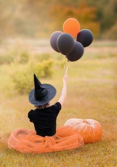 Conceito de halloween jovem bruxa de chapéu preto com balões e uma grande abóbora