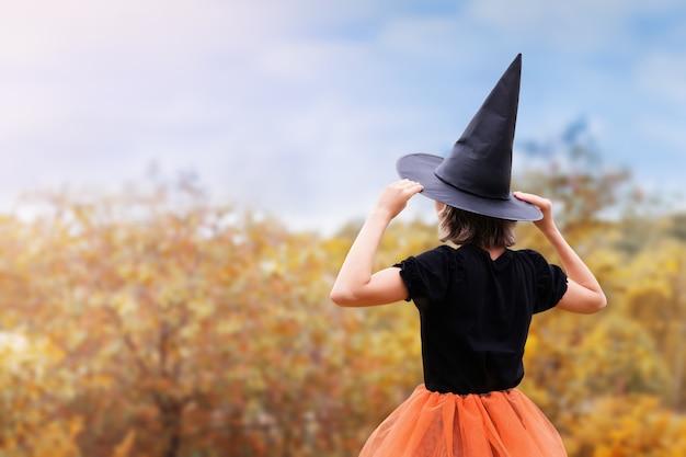 Conceito de halloween jovem bruxa de chapéu preto olhando para a natureza