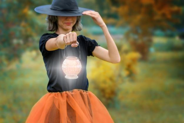 Conceito de halloween jovem bruxa sorridente de preto com lanterna brilhante