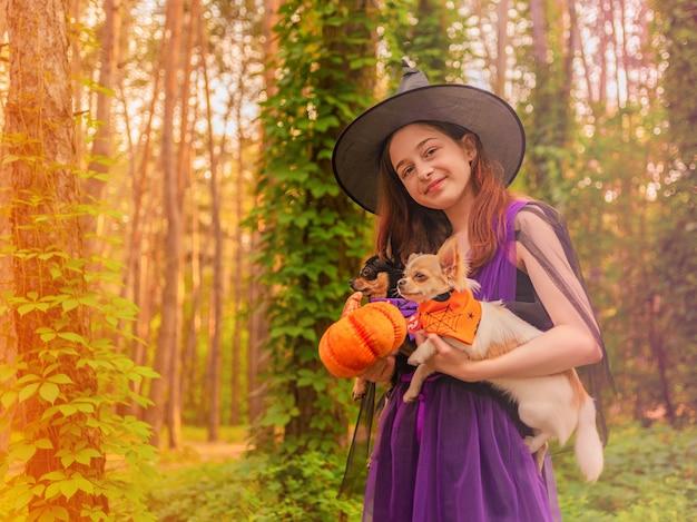 Conceito de halloween. jovem garota com uma fantasia de halloween com dois cachorros chihuahua na floresta.