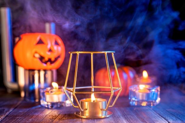 Conceito de halloween, lanterna de abóbora laranja e velas em uma mesa de madeira escura com fumaça laranja-azulada ao redor do fundo, doce ou travessura, close-up