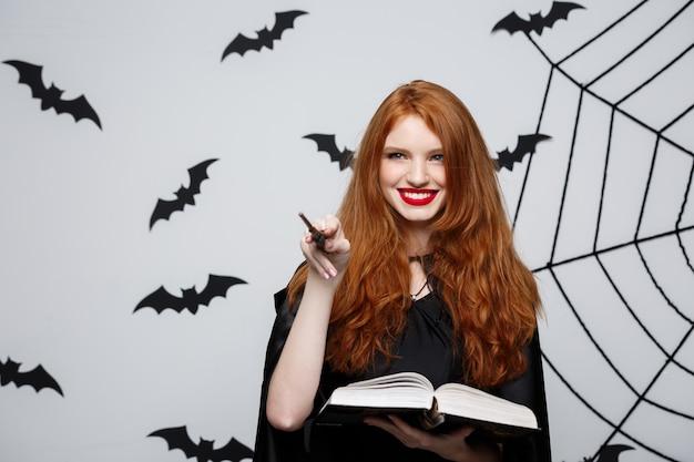 Conceito de halloween - linda bruxa brincando com uma vara mágica e um livro mágico na parede cinza.