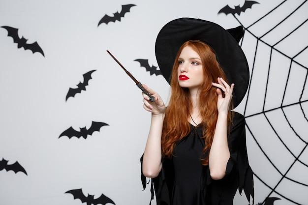 Conceito de halloween - linda bruxa brincando com uma vara mágica na parede cinza.