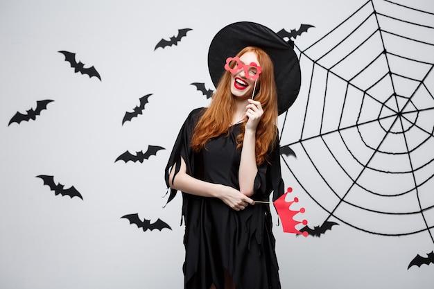 Conceito de halloween - lindas garotas em vestidos de bruxa pretos segurando adereços de festa.
