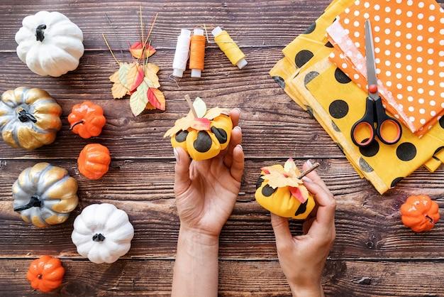 Conceito de halloween. mulher com as mãos segurando o artesanato de abóboras têxteis faça você mesmo sobre o fundo de madeira, vista superior plana lay